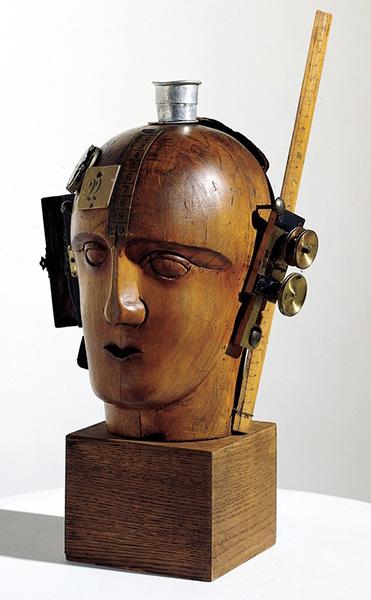 Mechanischer Kopf - Raoul Hausmann Marotte de coiffeur en bois et divers objets fixés dessus : gobelet téléscopique, un étui en cuir, tuyau de pipe, carton blanc portant le chiffre 22, un morceau de mètre de couturière, un double décimètre, rouage de montre, un rouleau de caractère d'imprimerie Format : 32,5 x 21 x 20 cm